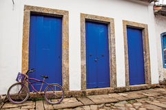 Monte en bicicleta delante de puertas azules cerradas y de la acera de piedra en Paraty Foto de archivo