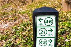 Monte en bicicleta el fingerpost que muestra las direcciones a través de las dunas en Holanda septentrional Imagenes de archivo