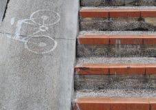 Monte en bicicleta el icono del símbolo de la muestra en la nueva trayectoria estrecha concreta gris de la cuesta Fotografía de archivo