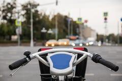 Monte en bicicleta el manillar, la palanca de freno y el primer del belio sobre avenida borrosa Fotografía de archivo libre de regalías