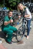 Monte en bicicleta el mecánico y al cliente en la tienda de la bici que da los pulgares para arriba Imagen de archivo libre de regalías