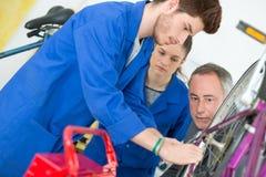 Monte en bicicleta el mecánico y a los aprendices que reparan la bici en taller Fotografía de archivo libre de regalías