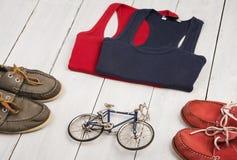 monte en bicicleta el modelo, zapatos, camisas, botella de agua en el de madera blanco Fotografía de archivo libre de regalías