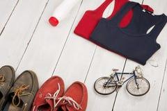 monte en bicicleta el modelo, zapatos, camisas, botella de agua en el de madera blanco Fotos de archivo libres de regalías