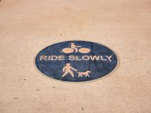Monte en bicicleta el paseo peligro lentamente la señal en el pavimento imagen de archivo libre de regalías
