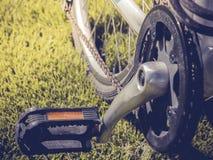 Monte en bicicleta el pedal con un contexto de la hierba artificial Imágenes de archivo libres de regalías