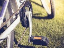 Monte en bicicleta el pedal con un contexto de la hierba artificial Imagen de archivo libre de regalías