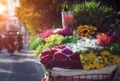 Monte en bicicleta el ramo de la flor de la venta al lado del camino en Hanoi Vietnam Imagenes de archivo