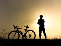 Monte en bicicleta el soporte del jinete en la colina que mira la luz del sol y relájese Fotos de archivo