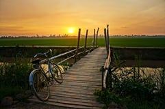 Monte en bicicleta en la cerca de madera del puente en la puesta del sol Foto de archivo libre de regalías