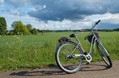 Monte en bicicleta estacionado en el borde de la carretera al lado del campo: Suecia Imágenes de archivo libres de regalías