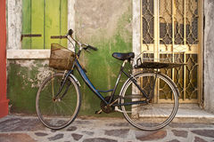 Monte en bicicleta inclinarse contra la pared colorida, Burano, Italia Fotos de archivo