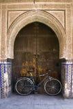 Monte en bicicleta inclinarse contra una puerta bajo una arcada imagenes de archivo