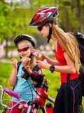 Monte en bicicleta a las muchachas con la mochila que comen el cono de helado en parque Imagen de archivo libre de regalías