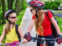 Monte en bicicleta a las muchachas con la mochila que completa un ciclo en carril de la bici Foto de archivo libre de regalías