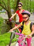 Monte en bicicleta a las muchachas con la mochila que completa un ciclo en carril de la bici Fotografía de archivo libre de regalías