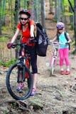 Monte en bicicleta a las muchachas con la mochila que completa un ciclo en parque del verano Imagenes de archivo