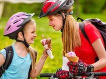 Monte en bicicleta a las muchachas que completan un ciclo comiendo el cono de helado en parque Imágenes de archivo libres de regalías