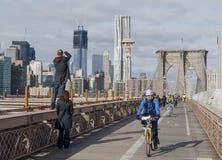 Monte en bicicleta los jinetes y a los turistas que disfrutan de un día en el puente de Brooklyn Foto de archivo libre de regalías