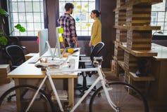 Monte en bicicleta por el escritorio mientras que los compañeros de trabajo que discuten en fondo Imagen de archivo