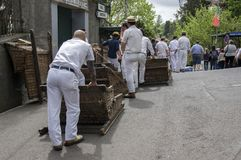Monte, Funchal / MADEIRA - April 22, 2017: Men with traditional white uniform, straw boaters and with basket cars Stock Photos
