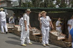 Monte, Funchal / MADEIRA - April 22, 2017: Men with traditional white uniform, straw boaters and with basket cars Royalty Free Stock Image