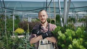 Monte la cámara El jardinero barbudo mira y sonríe la cámara Un día soleado en invernadero agrícola Retrato metrajes