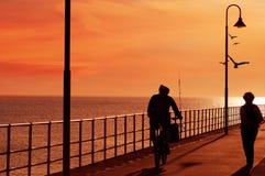 Monte le long de la jetée au coucher du soleil pour aller pêcher Photos libres de droits