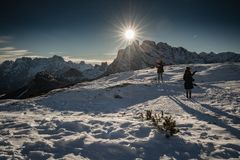 Monte Piana, Italy - January 1, 2019 : silhouette of women hiking in scenic snowy dolomites mountains, with direct sunlight. Monte Piana, Italy - January 1, 2019 royalty free stock photos