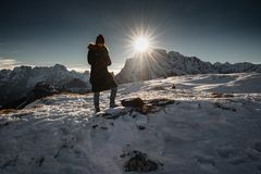 Monte Piana, Italy - January 1, 2019 : silhouette of women hiking in scenic snowy dolomites mountains, with direct sunlight. Monte Piana, Italy - January 1, 2019 royalty free stock photography