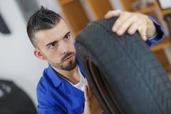 Monte pneus o mecânico que verifica a profundidade de passo no pneu de carro imagem de stock
