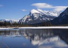 Monte Rundle reflejado en las aguas heladas de los lagos bermellones Imagen de archivo libre de regalías