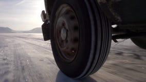 Monte sur la glace du lac et de beaucoup de neige La roue arrière de la voiture banque de vidéos