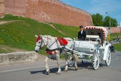Monte sur un chariot hippomobile en dehors des murs de Kremlin Veliky Novgorod images libres de droits