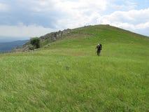 Monte verde e homens Fotografia de Stock