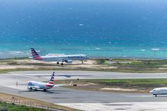 American Airlines aircraft landing while another waits to depart royalty free stock photos
