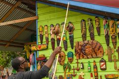 Young male vendor selling wall art wood carvings at craft market stock photo