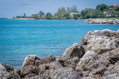 Coastline landscape in Montego Bay Jamaica with American Airlines aircraft landing in background. Montego Bay, Jamaica - March 19 2018: Coastline landscape in royalty free stock image