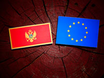 Montenegrin flag with EU flag on a tree stump isolated. Montenegrin flag with EU flag on a tree stump Royalty Free Stock Image