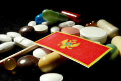 Montenegrin flag with lot of medical pills isolated on black bac Stock Images