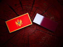 Montenegrin flag with Qatari flag on a tree stump isolated Stock Images