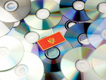 Montenegrin flag on top of CD and DVD pile isolated on white. Montenegrin flag on top of CD and DVD pile isolated Stock Image