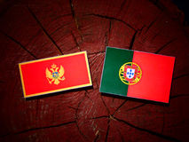 Montenegrinische Flagge mit portugiesischer Flagge auf einem Baumstumpf lokalisiert stockfoto
