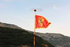 Montenegrinsk flagga över bergen mot himlen arkivbild