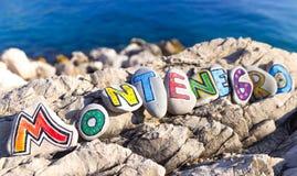 Montenegro-Aufschrift gemacht von gemalten Steinen auf Felsen, Seehintergrund Lizenzfreie Stockfotos