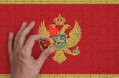 Montenegro flag is depicted on a puzzle, which the man`s hand completes to fold.  royalty free illustration