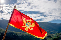 Montenegro flag. Flying in the background of the mountains Stock Photography