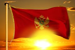 Montenegro flag weaving on the beautiful orange sunset with clouds background. Montenegro flag weaving on the beautiful orange sunset background royalty free stock photography