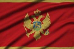 Montenegro-Flagge wird auf einem Sportstoffgewebe mit vielen Falten dargestellt Sportteamfahne lizenzfreie stockfotos