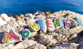 Montenegro inscription made of painted stones on rocks, sea background Royalty Free Stock Photos